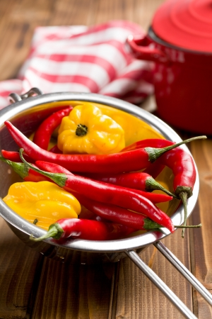 habanero: chili peppers and habanero in colander on wooden table