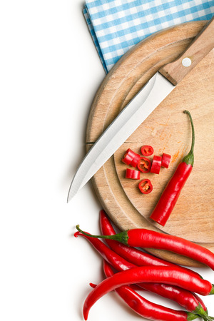 top view of chopped chili pepper on cutting board on white background photo