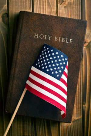 bless: holy bible with american flag on wooden background