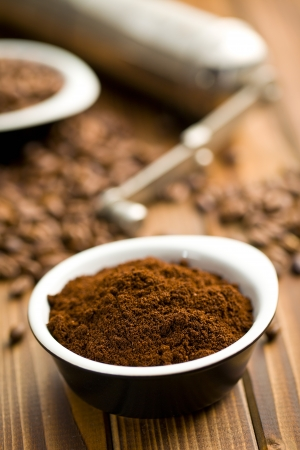 ground coffee in ceramic bowl on wooden table photo