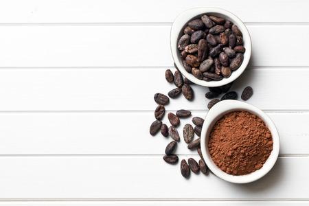 bovenaanzicht van cacaobonen en cacaopoeder in kommen Stockfoto