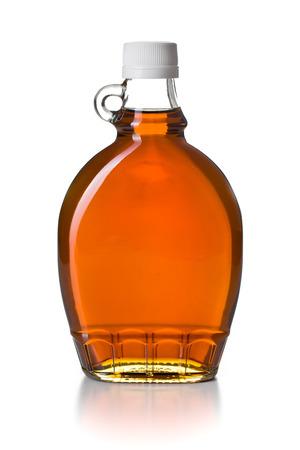 ahornsiroop in glazen fles op een witte achtergrond Stockfoto