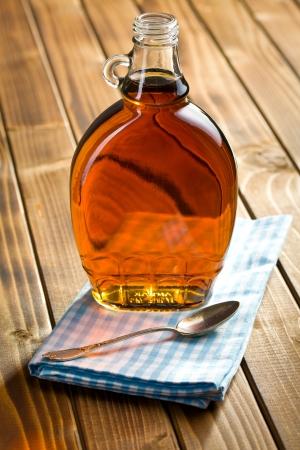 木製のテーブルの上のガラス瓶の中のメープル シロップ