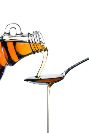 maple syrup: maple syrup pourin on spoon on white background