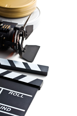 clapper board with movie light and film reel on white background photo