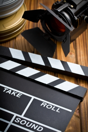 clapper board with movie light on wooden table photo