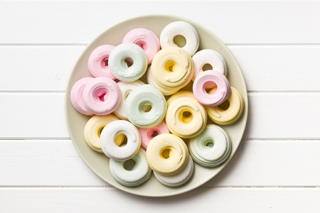 top view of colorful meringues on plate on white wooden table Stock Photo