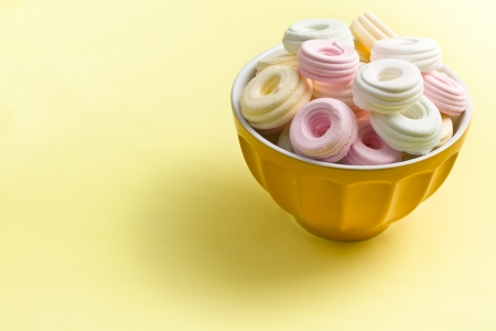colorful meringues in ceramic bowl on yellow background photo