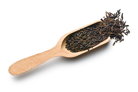 wild rice on wooden scoop on white background photo