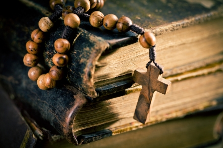 stack of old books with rosary beads photo