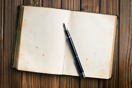 old diary: top view of old open book with fountain pen on wooden table