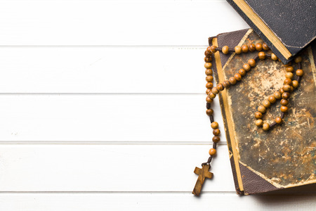 Wooden rosary beads with old book on wooden table photo