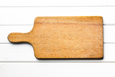 chopping: top view of wooden cutting board on white table