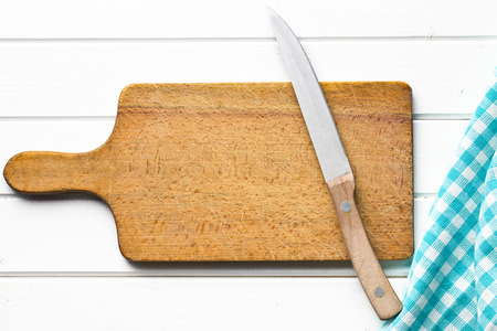 top view of cutting board with knife on white wooden table photo