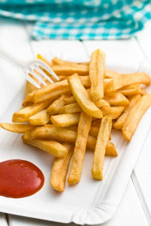 frites: french fries with ketchup on paper plate on white wooden table