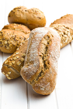 crust crusty: various breads on white wooden background