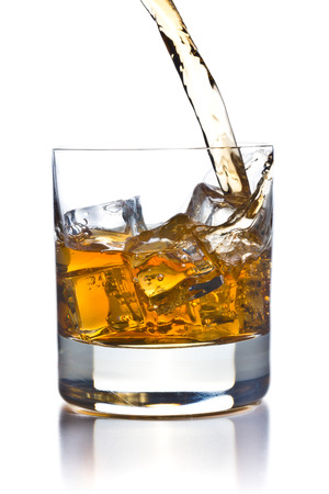 pouring whiskey in glass on white background photo