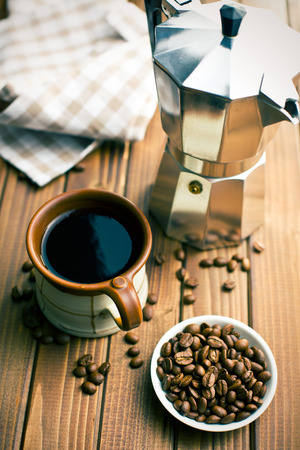 with coffee maker: coffee with coffee beans and coffee maker on wooden table