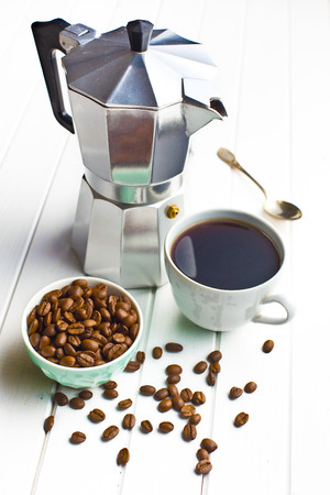 with coffee maker: coffee maker with cup of coffee and coffee beans on wooden background Stock Photo