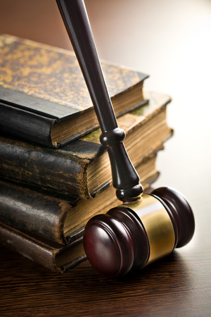 judge gavel with old books on wooden background photo
