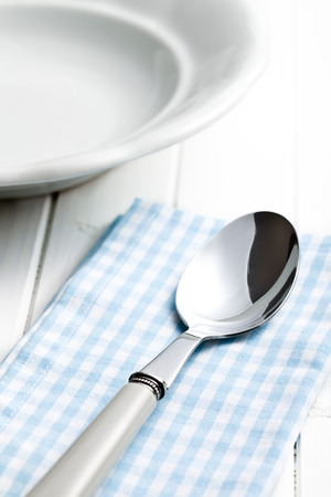 spoon and empty plate on white wooden table photo