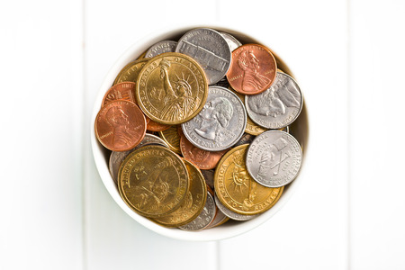 numismatics: U.S. coins in ceramic bowl on wooden table