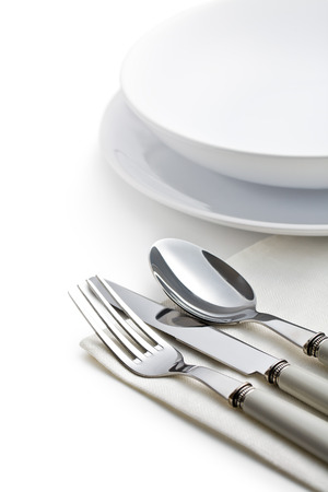 silver cutlery and plates on white background photo
