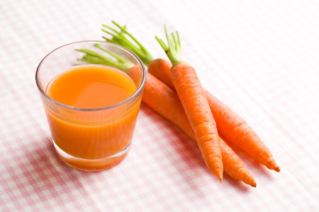 raw food: carrot juice in glass on checkered tablecloth