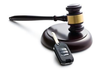 白い背景の上車のキーと裁判官の小槌