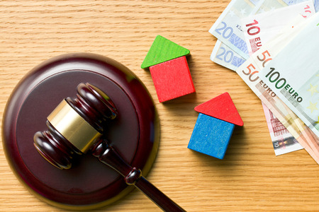 wooden houses with money and judge gavel on wooden table photo