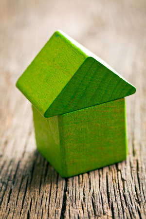 eco house: Green house made ​​from wooden cubes on wooden background