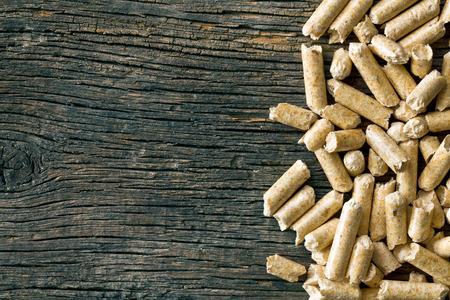 biomasa: los pellets de madera sobre fondo de madera vieja Foto de archivo