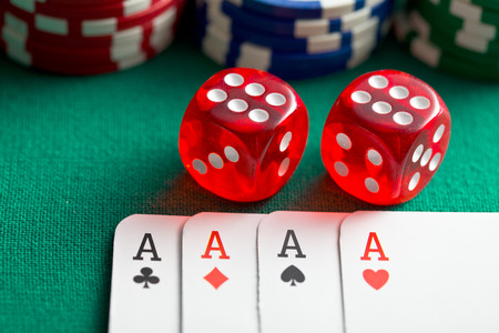 the red casino dice and poker cards on green table photo