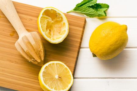 lemon lime: squeezed lemon fruit and citrus reamer on kitchen table
