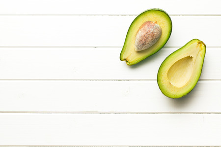 top view of halved avocados on wooden background Stock Photo