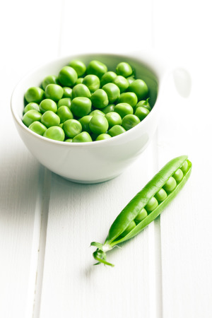 green peas in bowl on white wooden table photo