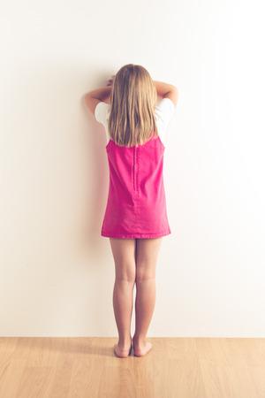 portrait of sad little girl standing near wall. studio shot photo