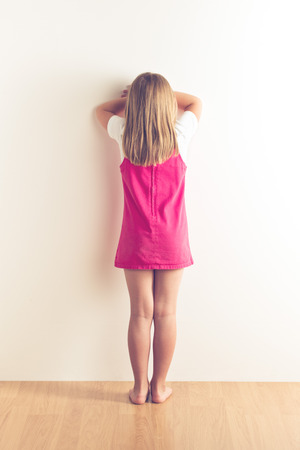 portrait of sad little girl standing near wall. studio shot