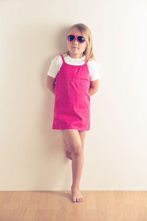 Little girl posing in front of a wall. Studio shot. photo