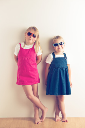 Two little girls posing in front of a walll. Studio shot. photo