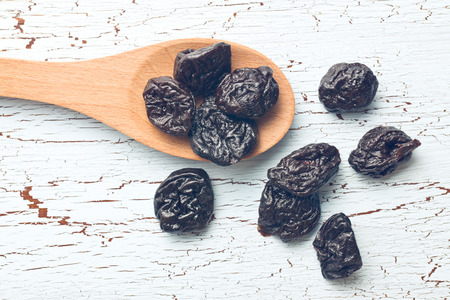 pitted prunes on old table Stock Photo