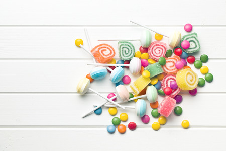 top view of colorful candy on white table photo