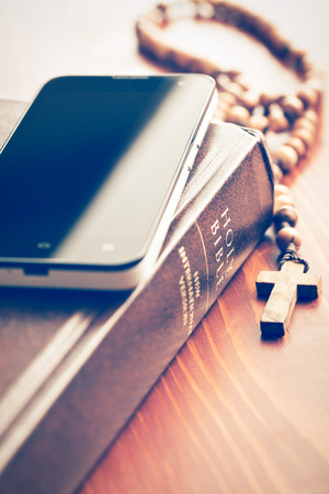the smartphone with holy bible and rosary photo