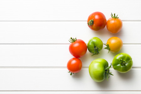 red and green tomatoes on white table photo