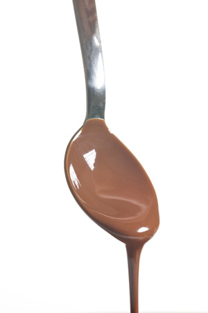 Chocolate poured into a spoon on white background photo