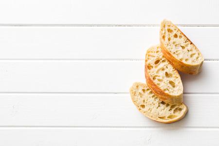 comiendo pan: rodajas ciabatta italiano sobre la mesa de madera blanca