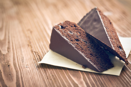 portion of sacher cake on wooden table Stockfoto