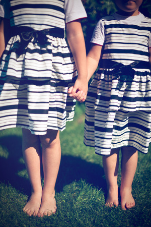 girls holding hands: Girls holding hands. Exterior shot.