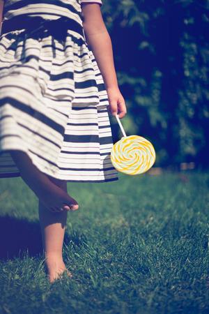 Little girl holding a lollipop in her hand. Closeup. photo