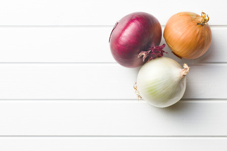 various onions on kitchen table Stock Photo